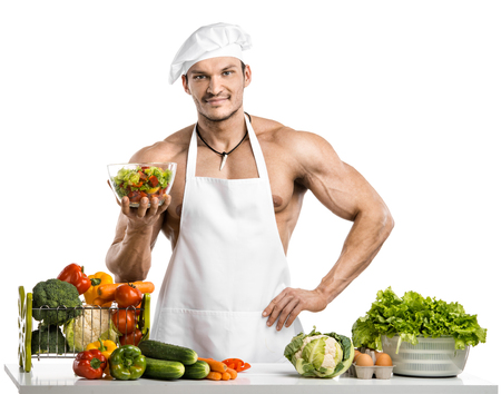 Man bodybuilder in white toque Blanche and cook protective apron, concoction vegetables and fruit , on whie isolated