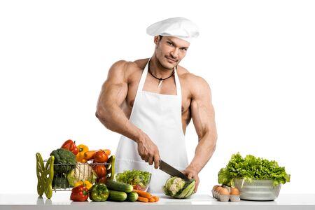 Bemannen Sie Bodybuilder im weißen Toque blanche und kochen Sie schützendes Schutzblech, Gebräugemüse und Frucht, auf whie Hintergrund, lokalisiert