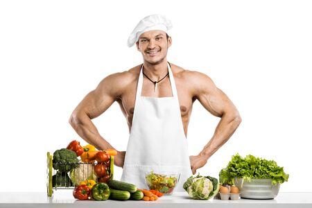 Bemannen Sie Bodybuilder im weißen Toque blanche und kochen Sie schützendes Schutzblech, Gebräugemüse und Lächeln, auf whie Hintergrund, lokalisiert