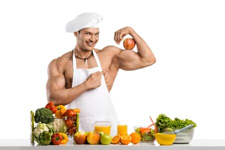 Man bodybuilder cook with apple on biceps, on whie background, isolated
