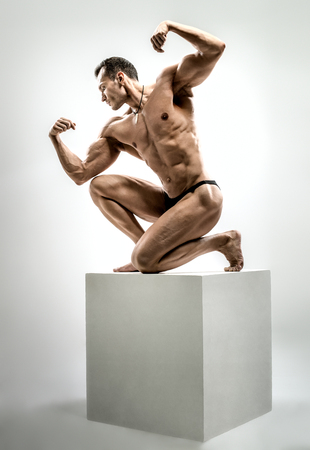 Very brawny athletic guy - bodybuilder,   pose on gray background