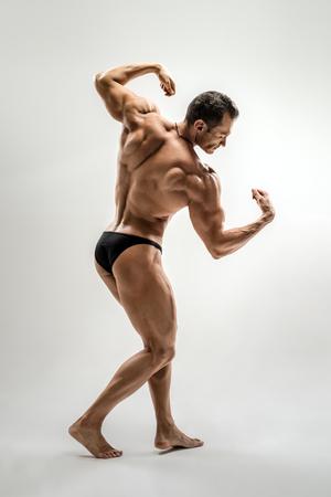 Very brawny athletic guy - bodybuilder,   pose on white background