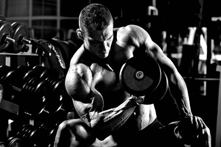 very power athletic guy bodybuilder , execute exercise with  dumbbells, in dark gym, black-and-white, grey, gray
