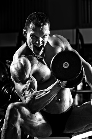 very power athletic guy , execute exercise with dumbbells, black-and-white photo