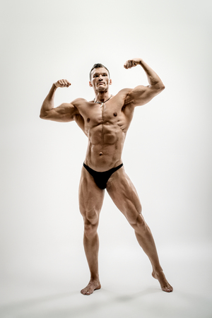 Very brawny athletic guy - bodybuilder,  pose on white background Stock Photo