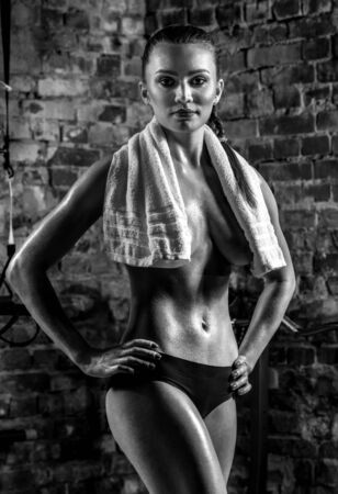young fitness woman in gym , in towel on brick background, vertical black-and-white photo