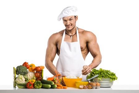 Man bodybuilder in white toque blanche and cook protective apron cooking cottage cheese and vegetables , on whie background, isolated