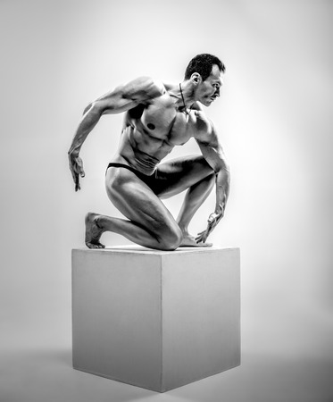 Very brawny athletic guy - bodybuilder, pose on gray background, black-and-white photo Stock Photo