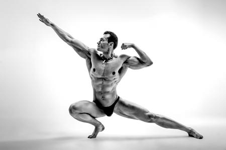 Very brawny athletic guy - bodybuilder, pose on white background, black-and-white photo