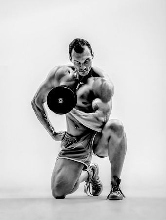 portrait very brawny athletic guy - bodybuilder,  with  weight, on white background, black-and-white photo