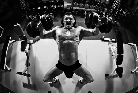 very power athletic guy bodybuilder , execute exercise press of dumbbells on pectoral muscle, in gym, black-and-white photo