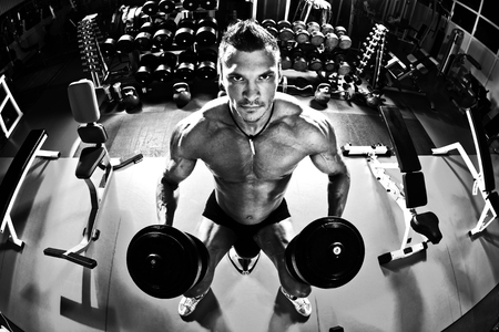 muscle athletic guy bodybuilder ,  with dumbbells , in gym, black-and-white photo