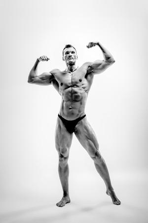 Very brawny athletic guy - bodybuilder,  pose on white background, black-and-white photo Stock Photo