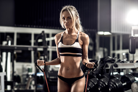 young fitness woman execute exercise in gym, horizontal photo
