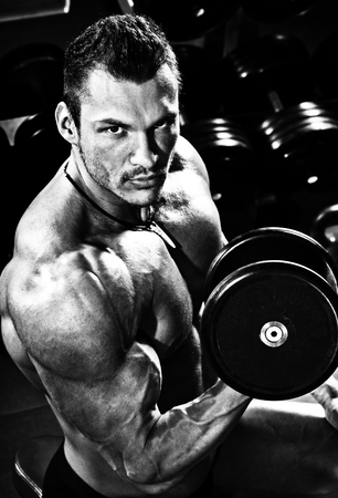 vertical close up portrait handsome guy bodybuilder, execute exercise with  dumbbells, in dark gym, black-and-white photo Stock Photo