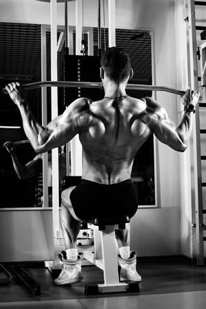 very power athletic guy bodybuilder,  execute exercise with gym apparatus, on broadest muscle of backб, black-and-white photo Stock Photo