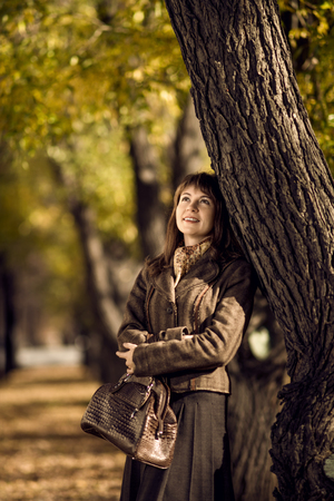 The happiness mature beautiful woman, walking outdoor in park, autumnal day