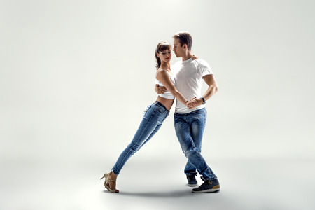 beauty couple dancing social danse ( kizomba or bachata or semba or taraxia) , on light grey background Stock Photo