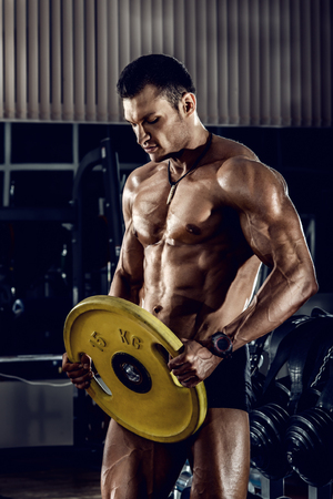 very power guy - bodybuilder, execute exercise with weight, inside gym, vertical photo