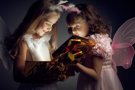 two little girl examine gift in fancy box, smile, on dark background, holiday concept Stock Photo