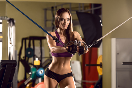 young fitness woman in gym perform exercise with Cable Crossover Machine, horizontal photo Stock Photo