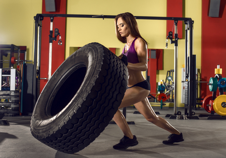 young fitness woman in gym perform exercise with car truck tire, horizontal photo Stock Photo