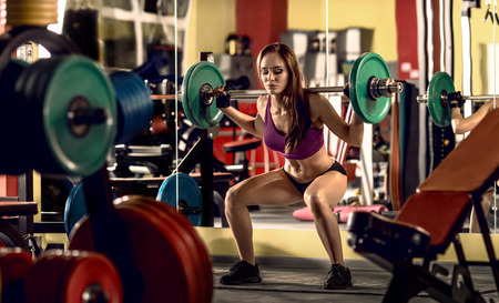 young fitness woman in gym perform exercise - squats with weight (bar), horizontal photo Stock Photo
