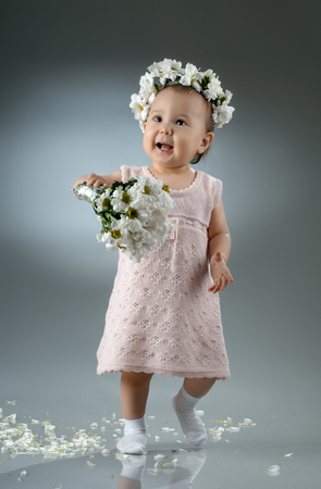beautiful little baby girl, with bouquet and diadem of flowers  Stock Photo