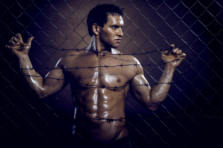 portrait muscular handsome sexy guy, on netting steel fence Stock Photo