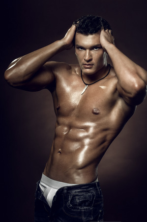 the very muscular handsome sexy guy on brown background, naked torso