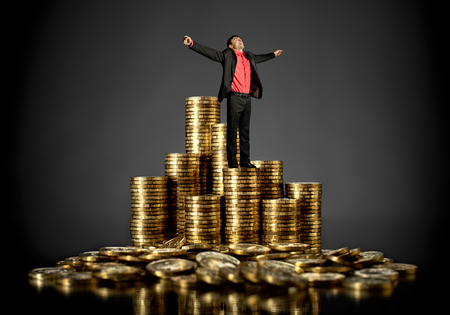 triumph businessman with many rouleau gold coin, winnings concept Stock Photo