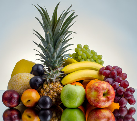 still life of big  heap multi-coloured fruits , on blue background, isolated Stock Photo