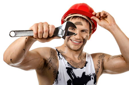 happy worker man, dirty in  safety helmet with big wrench  in hands, turn on and smile, on white background, isolated
