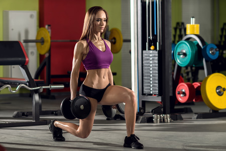 young fitness woman in gym perform exercise with dumbbells, horizontal photo