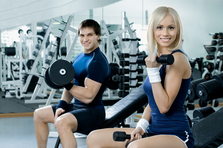 girl and guy exercise with dumbbells in gym, fitness concept
