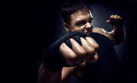muscular young guy street-fighter, cuff fist close up on camera, horizontal photo Stock Photo