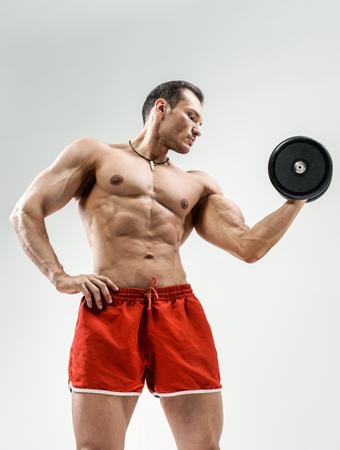 portrait  bodybuilder with weight, on grey background Stock Photo