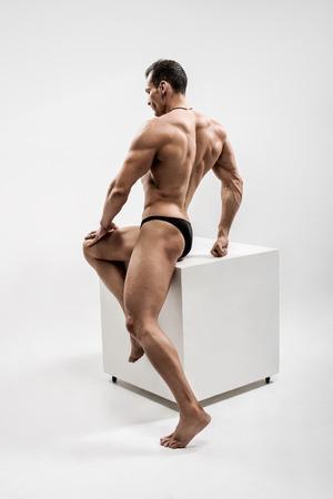 guy - bodybuilder,  pose on gray background