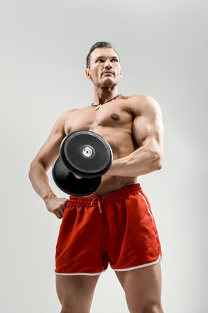 portrait  bodybuilder with weight, on grey background Stock Photo