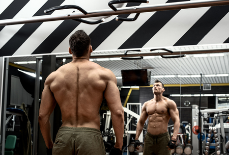 very power guy - bodybuilder, execute exercise with weight, inside gym, photo Stock Photo