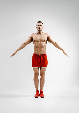 guy - bodybuilder athlete, does warm-up, hands in the parties, on gray background Stock Photo