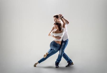 beauty couple dancing social danse ( kizomba or bachata or semba or taraxia) , on light-grey background