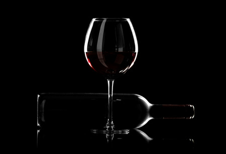 bottle and wine glass with red wine, horizontal photo on black background