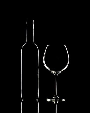 bottle and wine glass with red wine, vertical photo on black background
