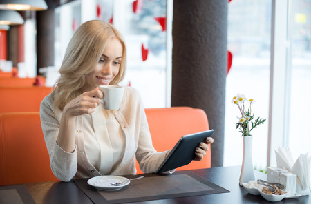 Very beautiful happy young woman sit in Cafe with flatbed computer, horizontal portrait Stock Photo