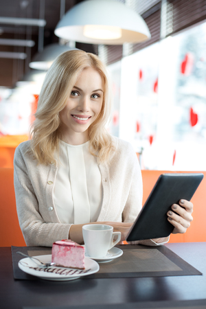 Very beautiful happy young woman sit in Cafe with flatbed computer, vertical portrait