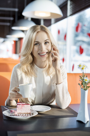 Very beautiful happy  young woman sit in  Cafe and talk on telephone, vertical portrait
