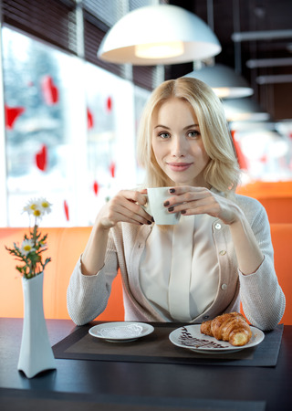 Beautiful happy young woman sit in Cafe and eating croissant with coffee or tea, vertical portrait