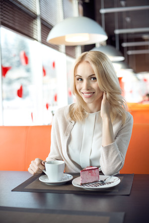 Very beautiful happy young woman sit in Cafe and eating dessert with coffee or tea, vertical portrait