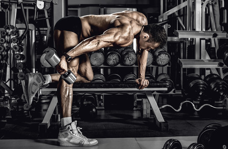 guy bodybuilder, perform exercise with dumbbell on triceps, in dark gym